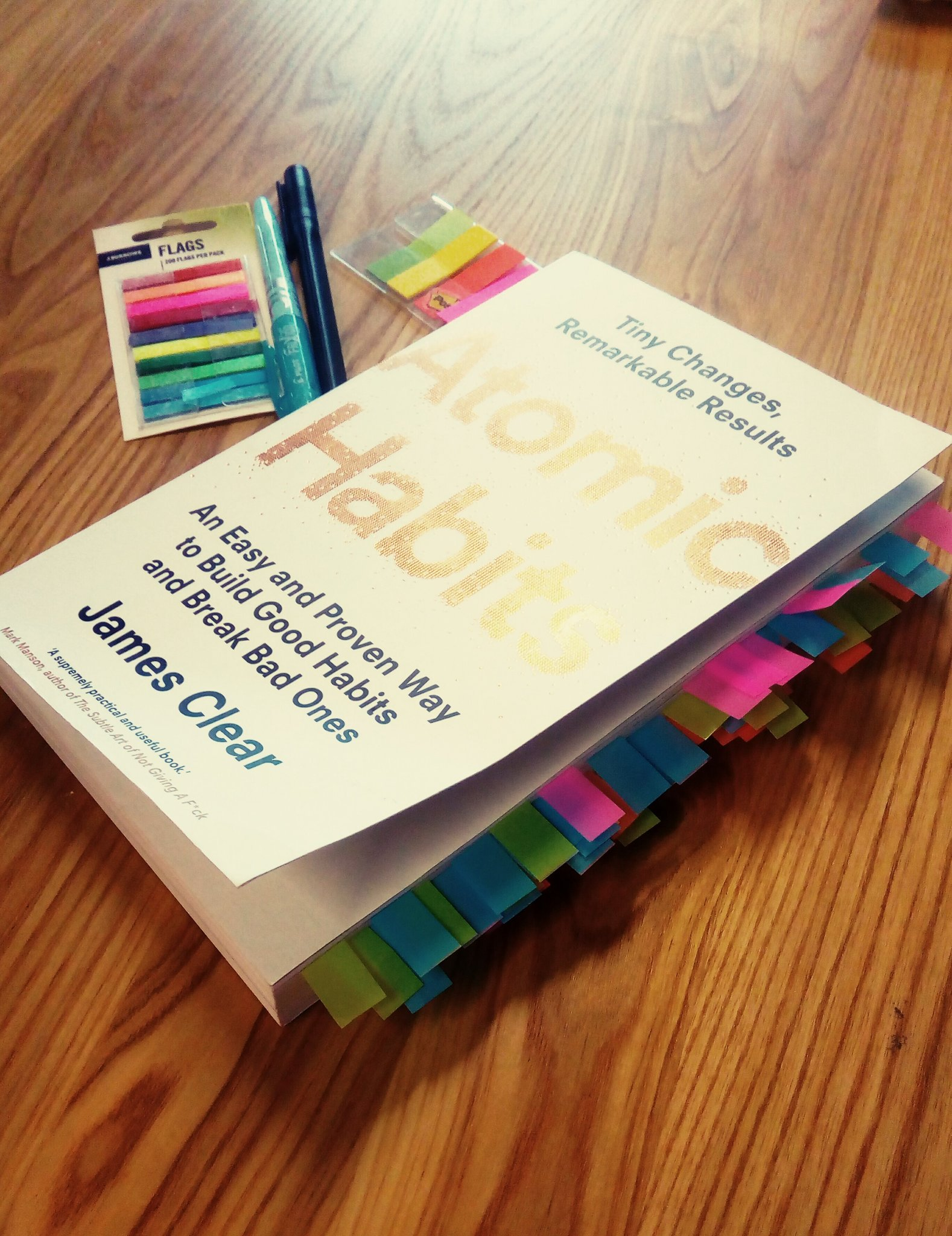 atomic habits book closed and filled with bright coloured index cards
